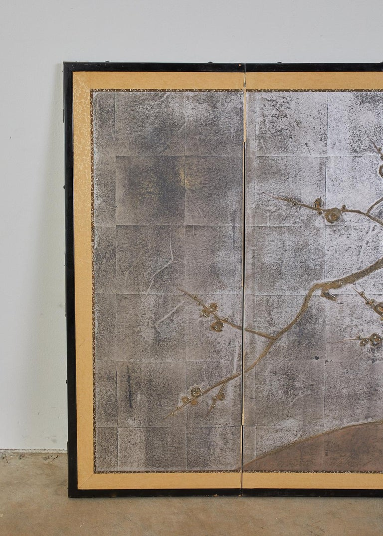 Unique Japanese four-panel folding byobu screen featuring a flowering prunus or plum tree over a dramatic silver leaf ground. The silver has a lovely faded patina that gives a moodiness to the art work which is painted in a moriage or raised pigment