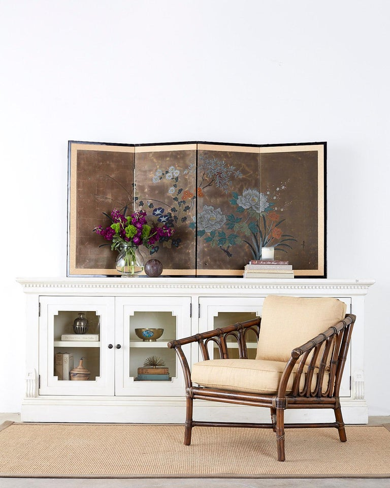 Interesting Japanese four-panel byobu screen displaying a selection of seasonal flowers. Peony, narcissus, morning glory, chrysanthemum and lily among pampas grass. Painted with ink and color on a gilt background of printed gilt squares. Signed