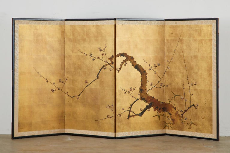 Showa period Japanese four-panel screen depicting a flowering prunus or plum tree in the spring. Ink and color pigments over gilt squares. Set in an ebonized wood frame with a silk brocade border. Signed and sealed on the right side. Made in the