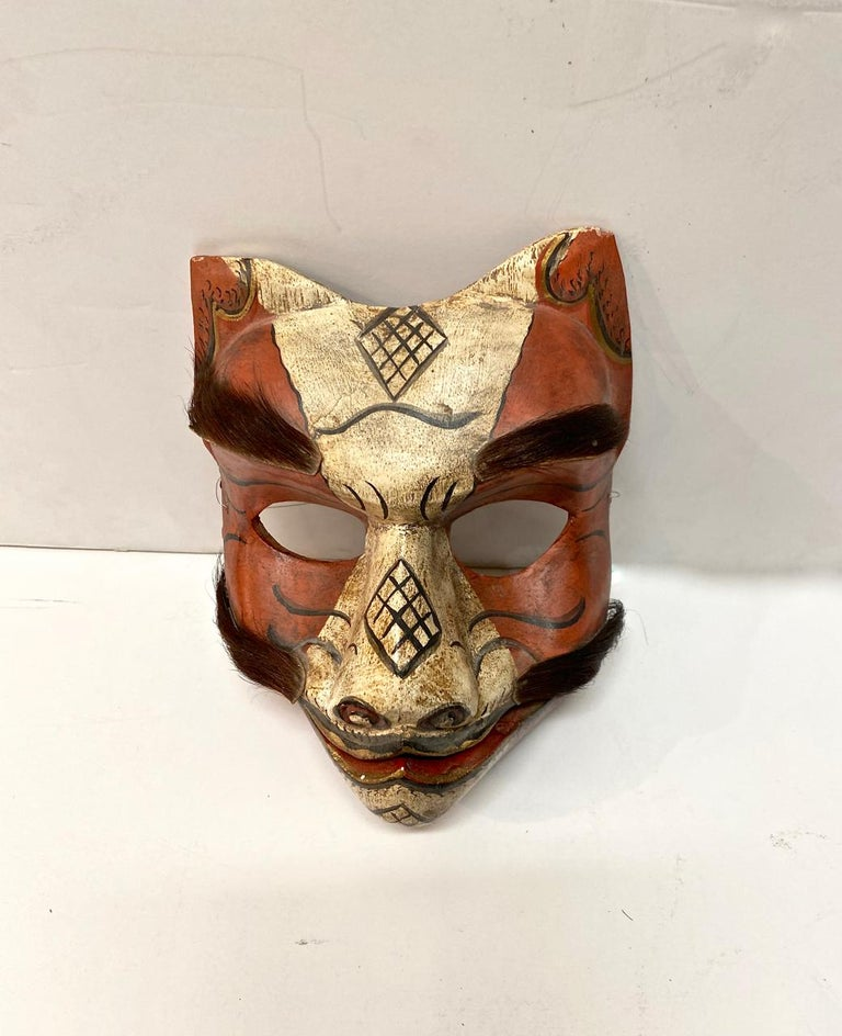 This is a wonderfully expressive and articulated fox mask. The mask dates to the first half of the 20th century and is in overall good condition. The fox's jaw is articulated and he is decorated with real fur for his eyebrows and mustache. In Japan