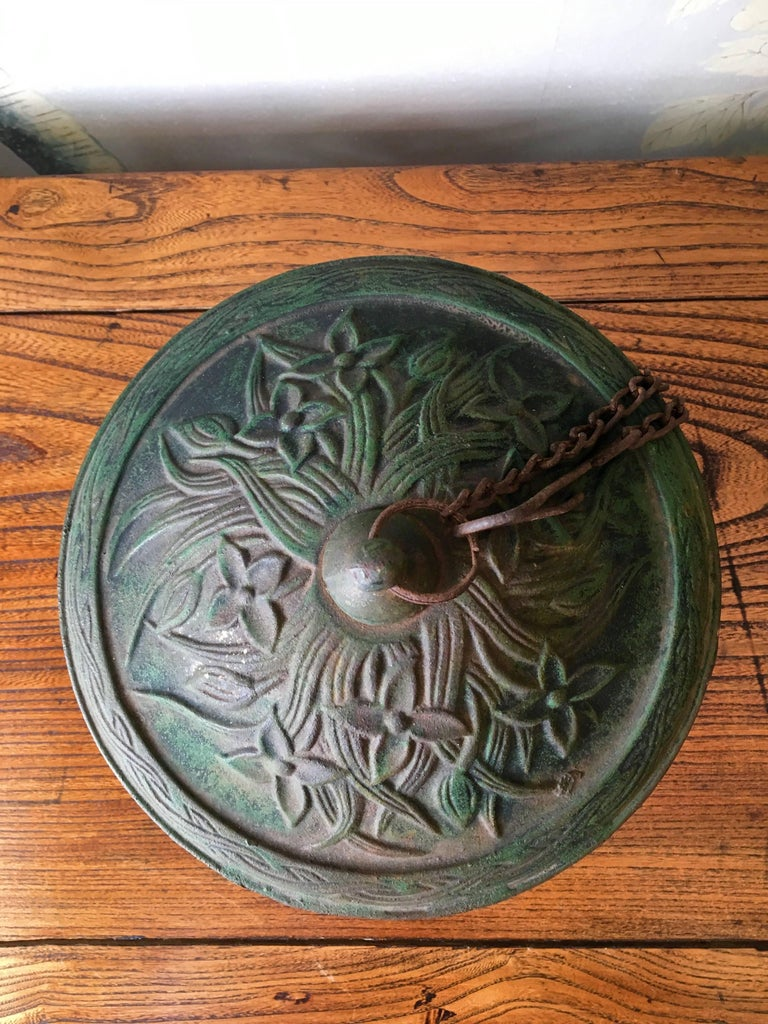 A vintage cast iron Japanese garden lantern with chain and hook for hanging.