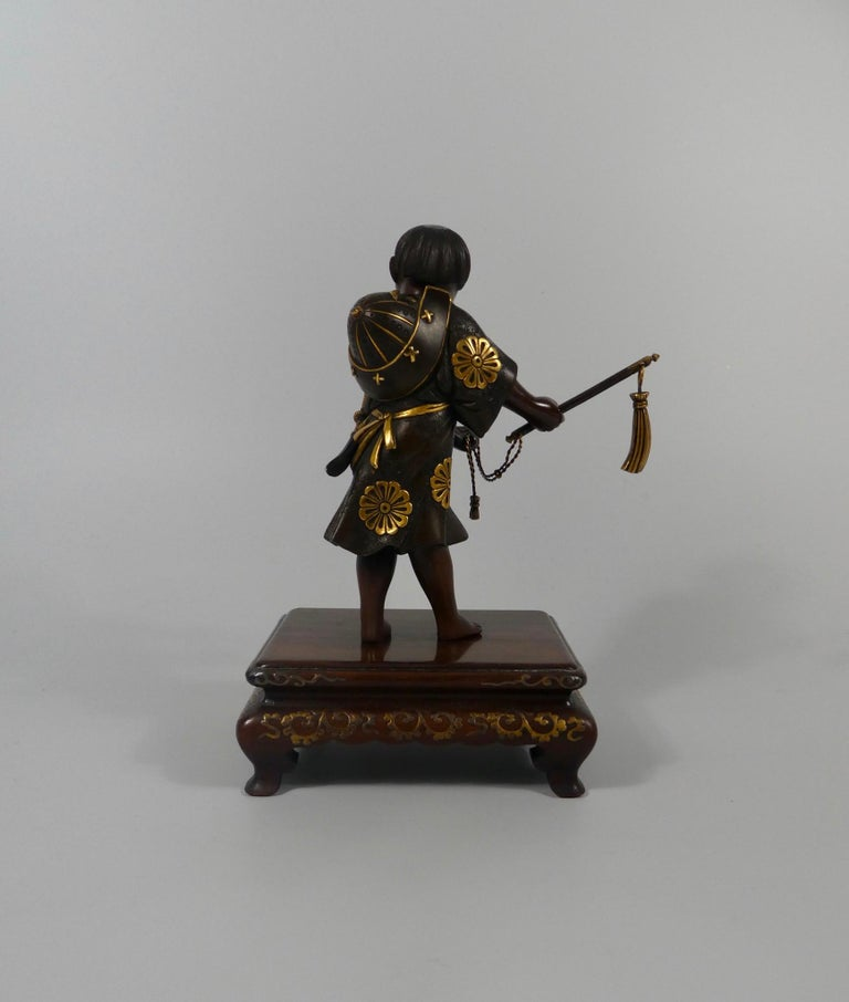 A fine Japanese bronze okimono, by Miyao Eisuke, Meiji Period (1868-1912). Charmingly modelled as a young, smiling boy, dressed as a Samurai. He stands, wearing a knee length tunic, cast and engraved with stylised floral motif, the flower heads