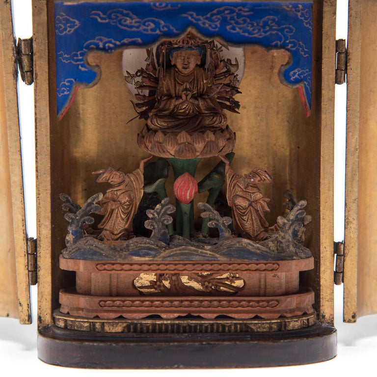 The simple exterior of even black lacquer that encases this Late 19th century Japanese traveling shrine belies the splendor within. The hinged doors open to reveal an intricately carved gilt figure of the bodhisattva Senju Kannon, or
