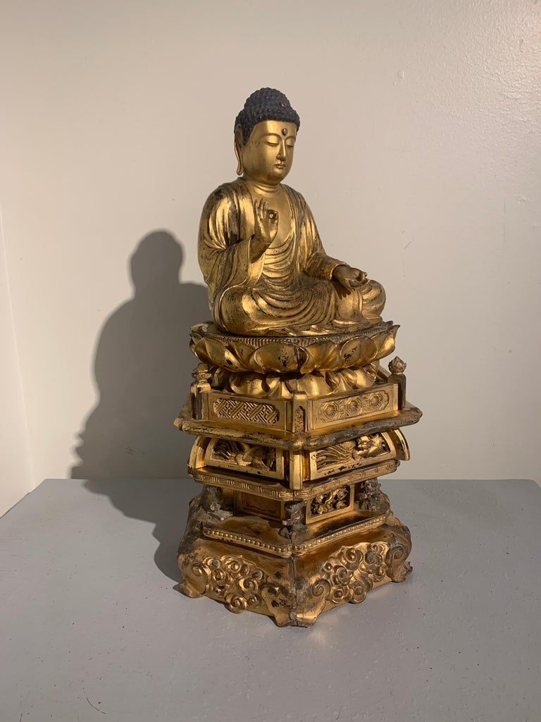 A magnificent Japanese carved and giltwood figure of the Medicine Buddha, Yakushi Nyorai, seated upon a double lotus pedestal supported by a multi-tiered stand, mid-Edo Period, late 18th century.  Yakushi Nyorai, as the Medicine Buddha is known in