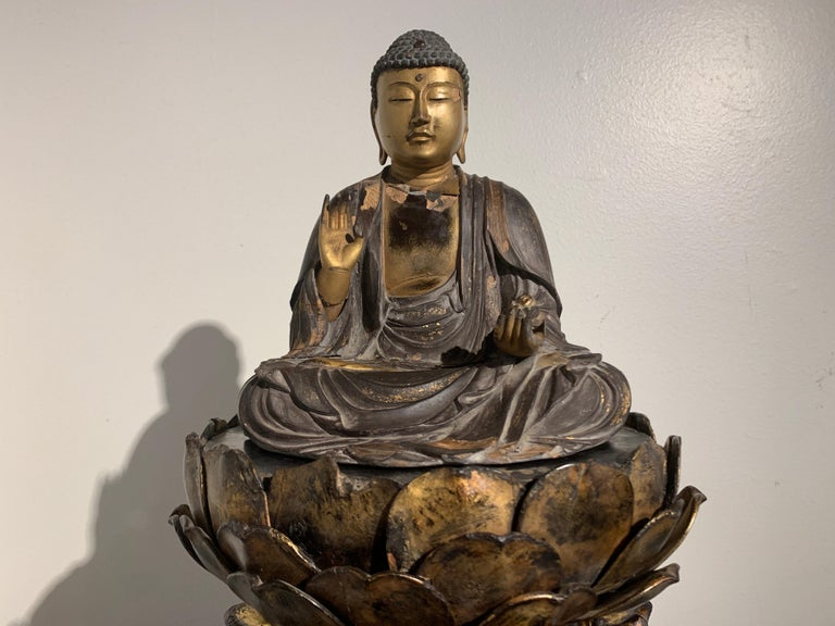 A striking Japanese late Muromachi Period (1333-1573) lacquered and giltwood figure of Yakushi Nyorai, the Medicine Buddha, seated upon an elaborate carved openwork lotus pedestal, Japan, mid-16th century.