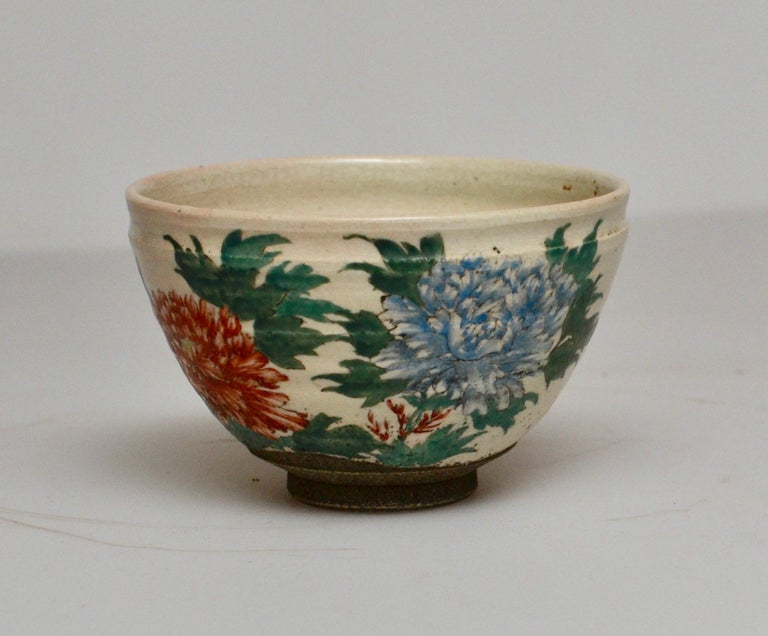 A late 19th-century Japanese glazed tea bowl with painted floral design.