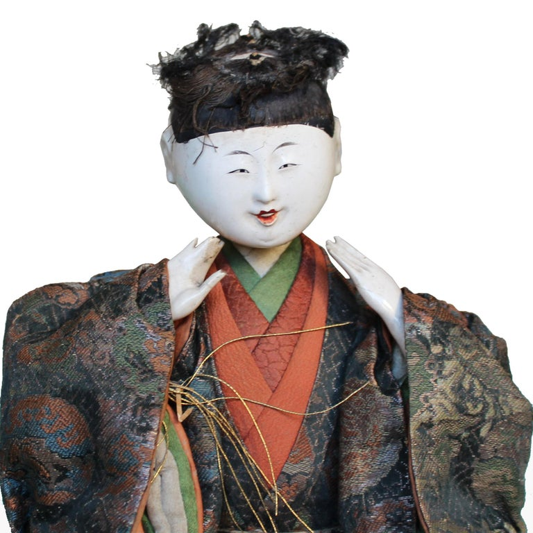 Master artisans skillfully crafted the Kyoto doll with white lacquered wood head and hands, dressed in Classic Japanese style clothes made from antique kimono textiles. Doll depicts one of the musicians in traditional Japanese Noh theatre. Meiji