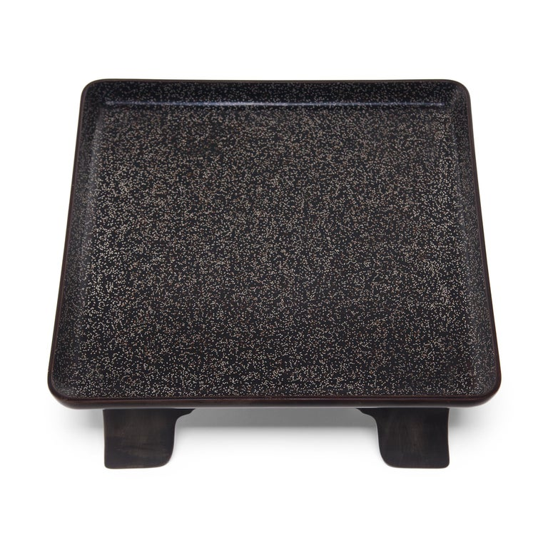 This late 19th century square Japanese tray exemplifies the refined style of Meiji-era tea ceremony objects. Elevated by a footed base, the tray is minimally decorated with an even, black lacquer finish. The shallow tray top is patterned with