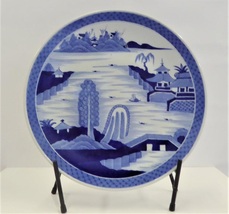Beautiful 1950s blue and white Japanese Imari charger depicting a serene hand painted scene of a village by river side with boats, a bridge and islands on the background. The rim in the back has stylized floral decoration. Beautifully hand painted