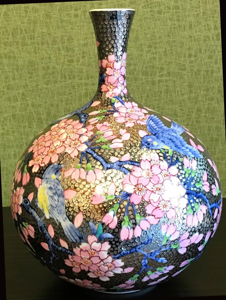 Contemporary gilded porcelain vase, intricately hand painted in pink and blue on an attractively shaped ovoid body with an elegant long neck, in textured gold background. This stunning piece is the work of an acclaimed and award-winning master