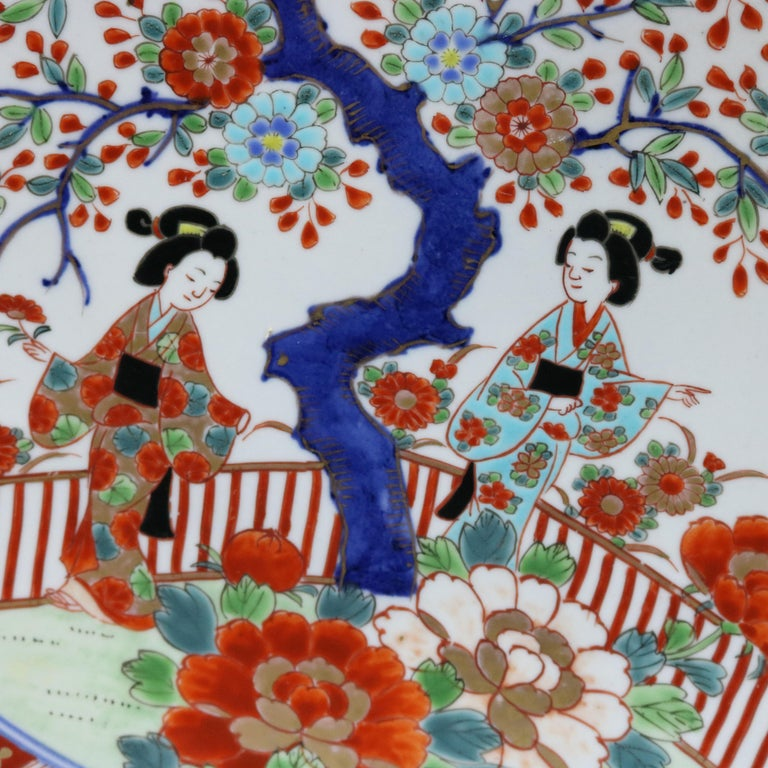 A Japanese Imari porcelain charger offers central garden scene with figures and tree with foliate decorated border, en verso chop marks and