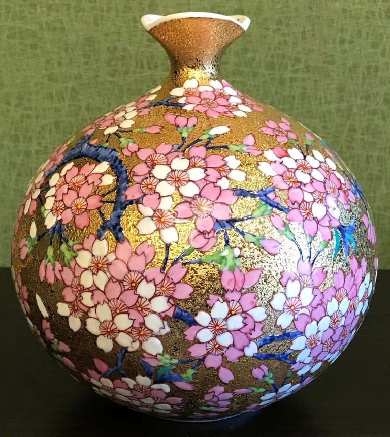 Imari contemporary gilded porcelain vase, intricately hand painted in pink, white and blue on an attractively shaped ovoid body with lotus flower shape opening. This stunning piece is the work of an acclaimed and award-winning master porcelain