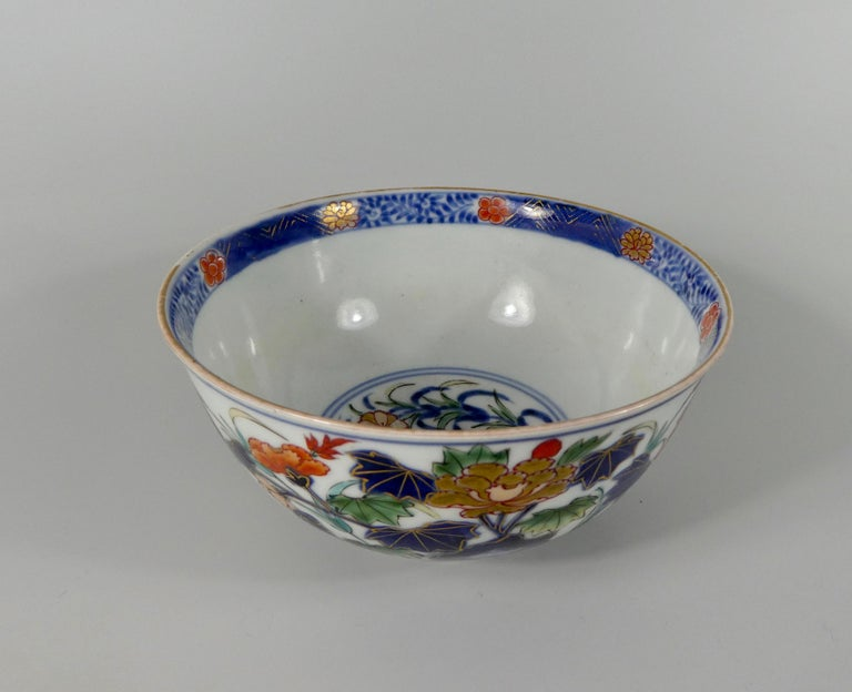 A fine Japanese porcelain bowl, Arita, late 17th-early 18th century. Beautifully painted in 'Imari' style, with a continuous scene of flowering plants growing amongst rocks, in underglaze blue, green, yellow, iron red, and heightened in gilt; above