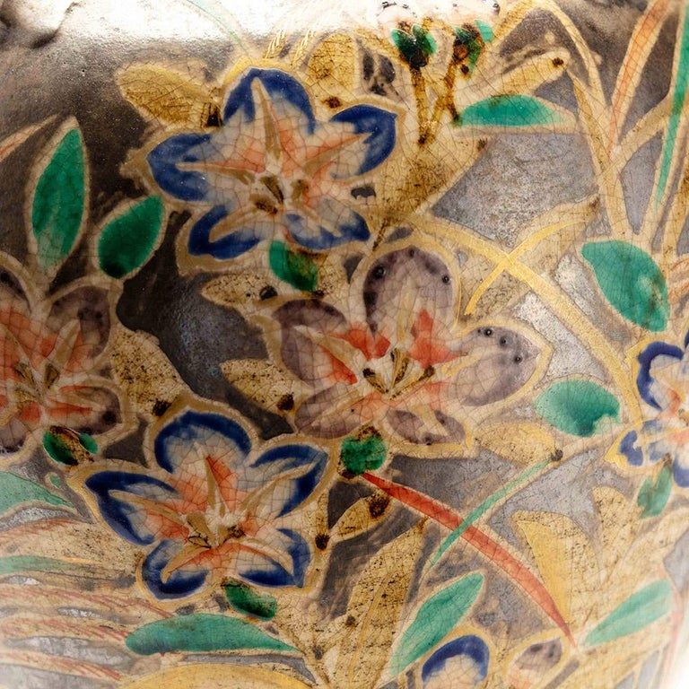 This Japanese Kenzan style vase has a classical shape with four small round handles. It has a colourful floral design of flowers and grasses. These have been hand painted in blue, green, purple and orange, on a silver gilt background that has a