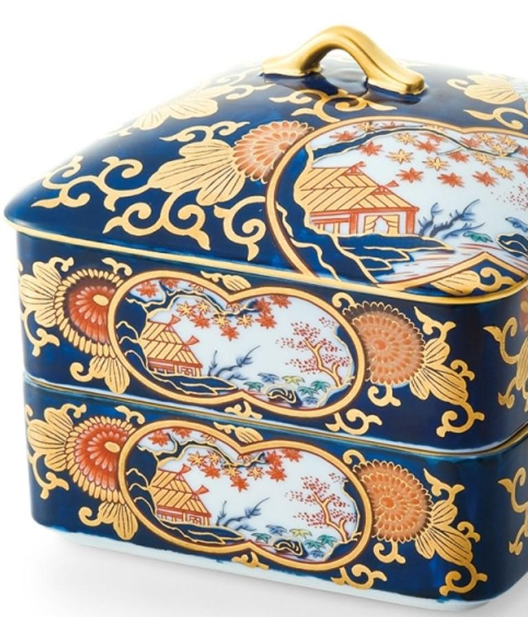 Contemporary Japanese KO-Imari style two tiered lidded decorative porcelain box, intricately hand painted in cobalt blue, red and green and generous application of gold on a pure white porcelain, characteristic of Ko-Imari style.  The attractive