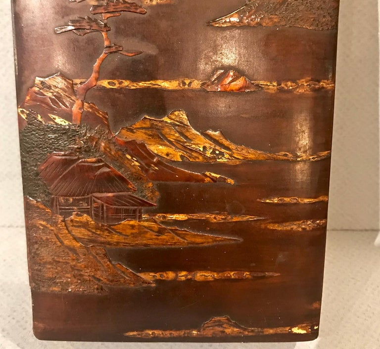 This Japanese writing box dates to circa 1950 and is detailed with a raised lacquer scene of mountains and village.