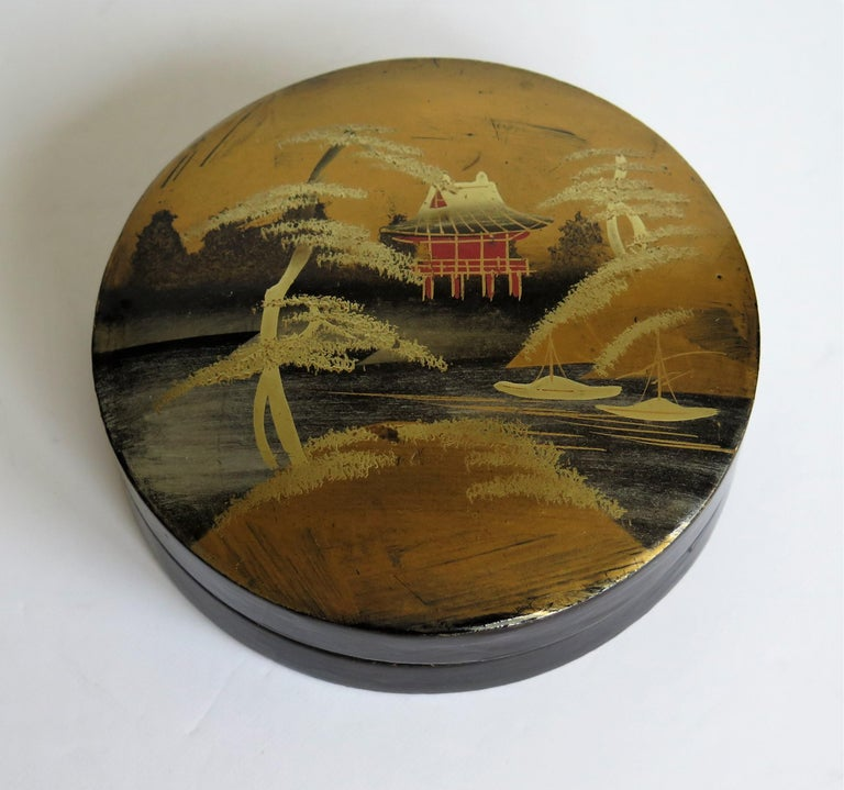 This is a beautiful papier mâché, circular lacquered lidded box, which we attribute to being made in Japan, very early in the 20th century, late Meiji period, circa 1900.