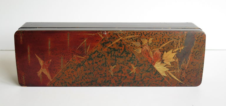 This is a beautiful papier mâché, lacquered lidded box, which we attribute to being made in Japan during the early 20th century, Taisho period, circa 1920.  The box has an oblong shape with a hinged slightly domed top and an original fitted lock