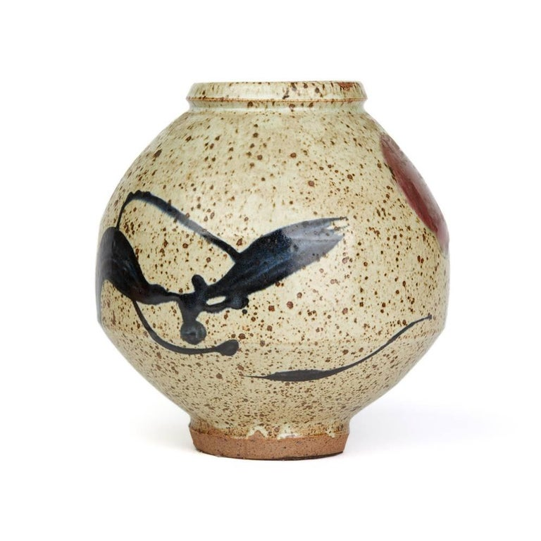 A stunning and stylish Studio Pottery vase, believed Japanese, of large bulbous shape decorated with stylized dancing figures in brushed glazes on a stone colored ground with tenmoku glaze spotting. The vase has an unglazed foot with an impressed