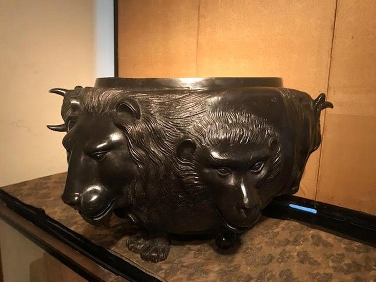 Japanese Meiji period bronze vessel with elaborately sculpted animal heads. Lion, ape and bull heads are surrounding the vessel. Made in Japan in the circa 1880s, the piece has a makers mark and a rich dark bronze patina. In great antique condition