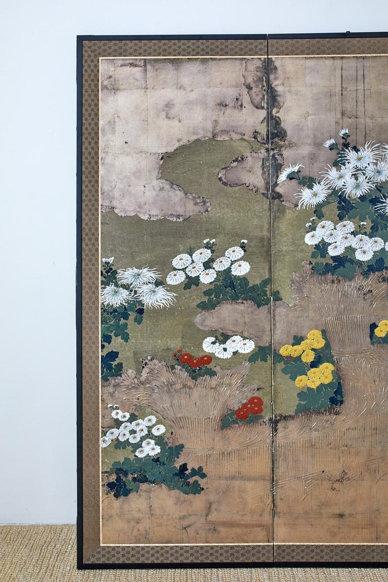 Extraordinary Japanese late Meiji period four panel screen depicting colorful chrysanthemums growing along a brushwood fence. The screen features extensive moriage (raised pigment) decoration on the fence and flowers that are difficult to appreciate