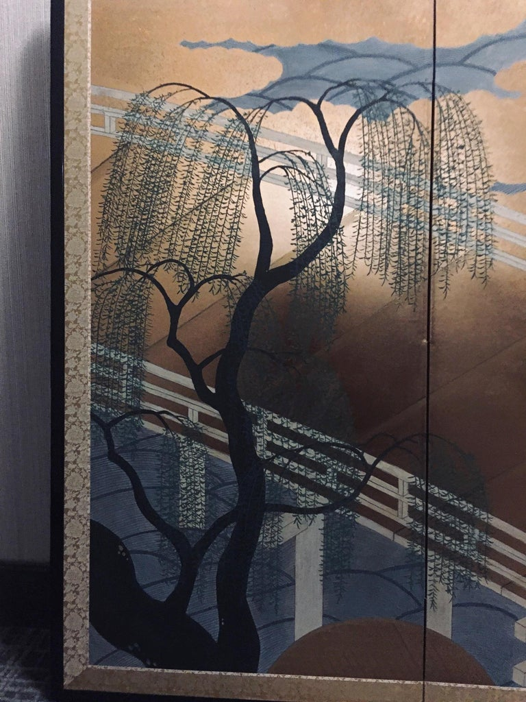 Japanese four panel screen depicting a bridge crossing a river and weeping willow trees. Richly decorated with gold leaf. Framed with a black lacquer frame with a rich brocade. Signature and stamp on the lower right corner. Made in the Late 20th