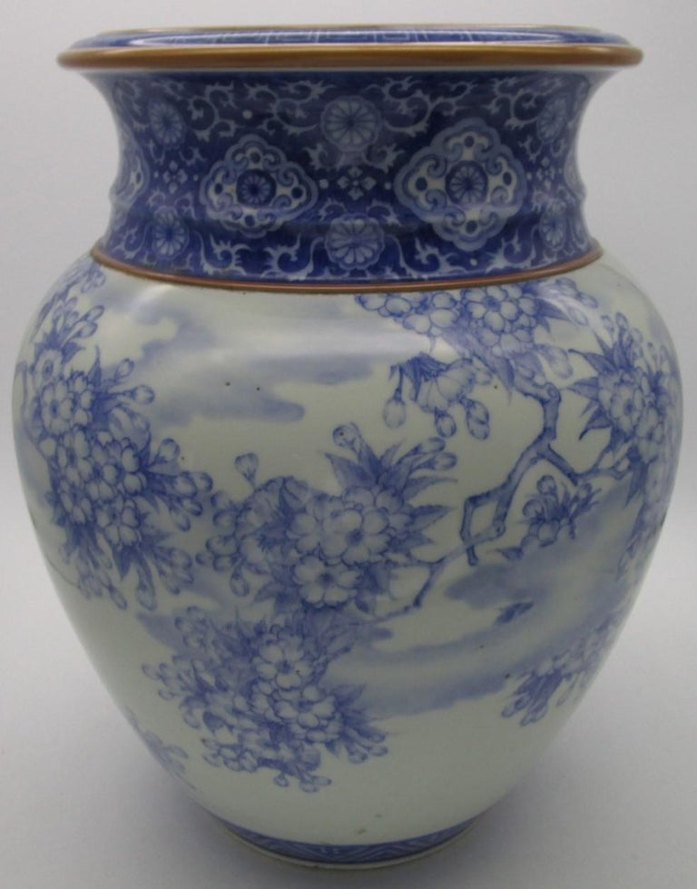 Japanese late-19th century Fukagawa porcelain vase in blue underglaze from Meiji period, (1868-1912,) in a stunning shape depicting intricate cherry blossoms decorating the body pleasantly contrasted by intricate and detailed geometric patterns