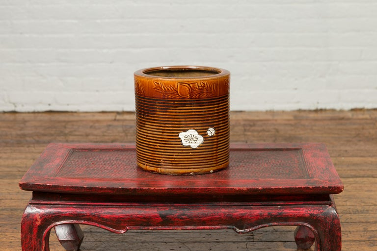 A Japanese Meiji period hibachi planter from the 19th century, with floral motifs and burnt orange patina. Created in Japan during the Meiji period, this hibachi was used for cooking or warming sake or tea. Presenting a cylindrical silhouette