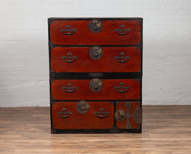 A Japanese Meiji period two-part tansu clothing chest from the 19th century, with round medallion hardware and butterfly accents. Born in Japan during the 19th century, this wooden tansu chest is a fine example of Japan's traditional mobile