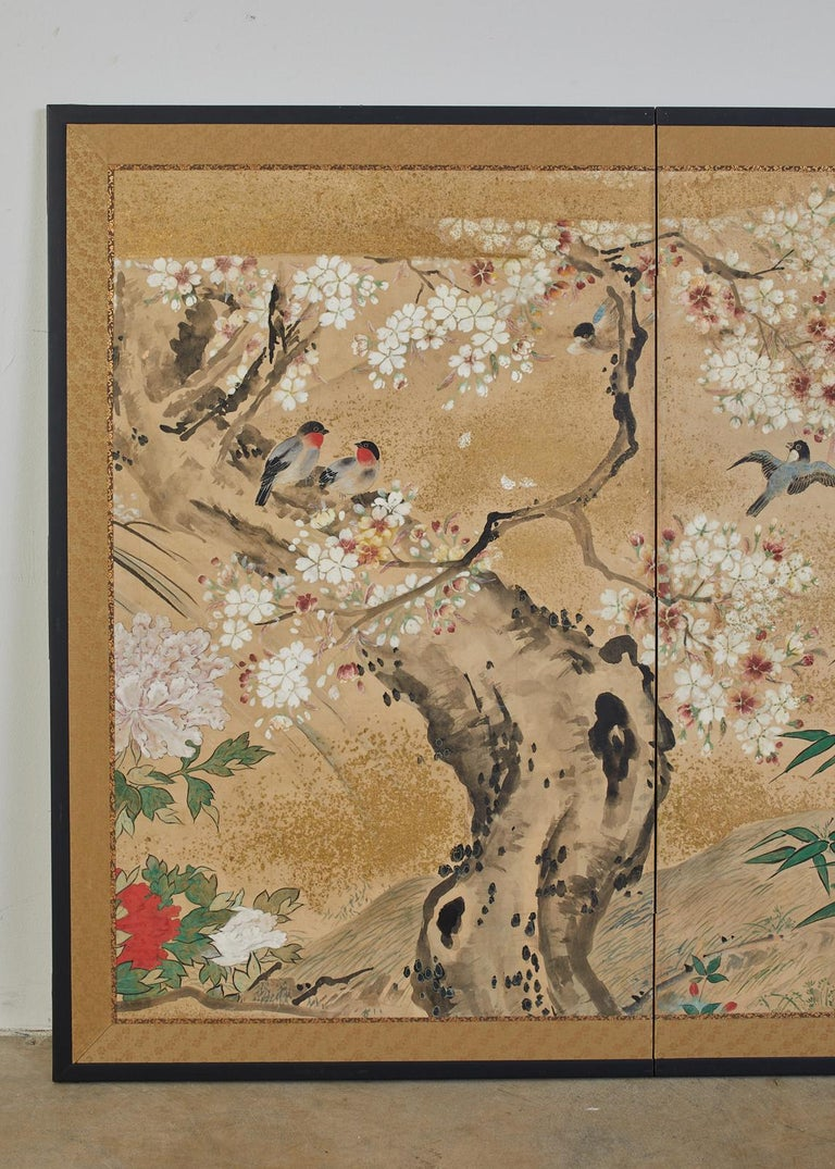 Exceptional Japanese Meiji period two-panel screen, circa 1900. Featuring songbirds amid sakura cherry trees and flowering peony. Made in the Nihonga School style on handcrafted mulberry paper. Ink and natural pigments with gold flecks decorate the