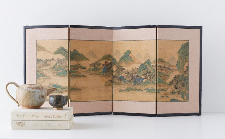 19th century mid-Edo period Japanese four-panel miniature screen. Depicting a beautifully painted Chinese blue and green landscape in the Nanga School or literati painting style. Ink and color pigments on silk mounted in a lacquered wood frame with