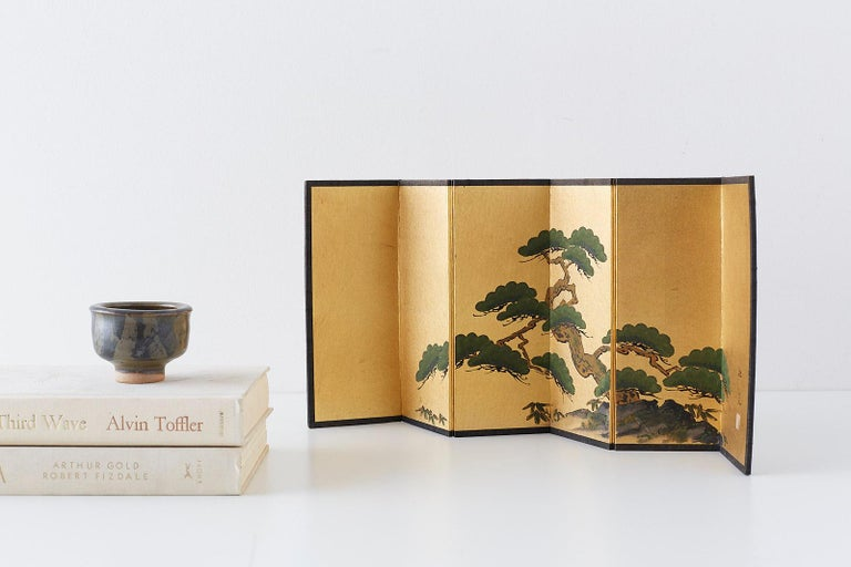 Diminutive Japanese six-panel screen in a miniature table size. Depicts an ancient pine with bamboo. Ink and color pigments on gilt metallic paper. Signed Shoku/Shokyo and one seal stamp. Printed paper verso of a scrolling vine and flower design