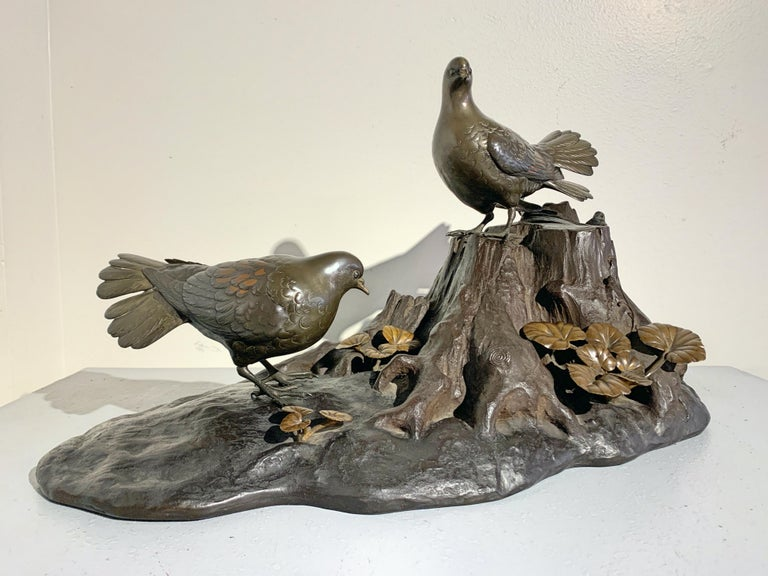 A wonderfully naturalistic and large Japanese Meiji period mixed metal okimono (ornamental sculpture) of a pair of oriental turtle doves perched on a gnarled tree trunk, signed Seifu, late 19th century, Japan. 