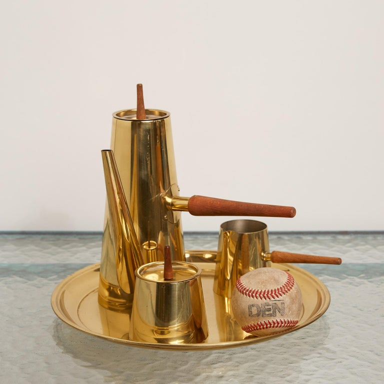A four-piece mid-century brass tea set. The forms each showcase elegant angles while the handles of the pots and lids are made of a beautiful, dark wood. Each piece sits on top of a brass tray with soft, round edges. Marked [Japan] on underside of