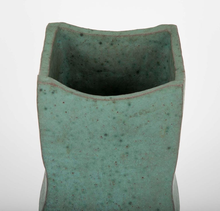 A beautifully conceived, thoroughly modern Japanese ceramic vase with wonderful muted turquoise glaze. The geometric upper portion above a round tapered unglazed base. An unusual and very compelling design. Marked on base.