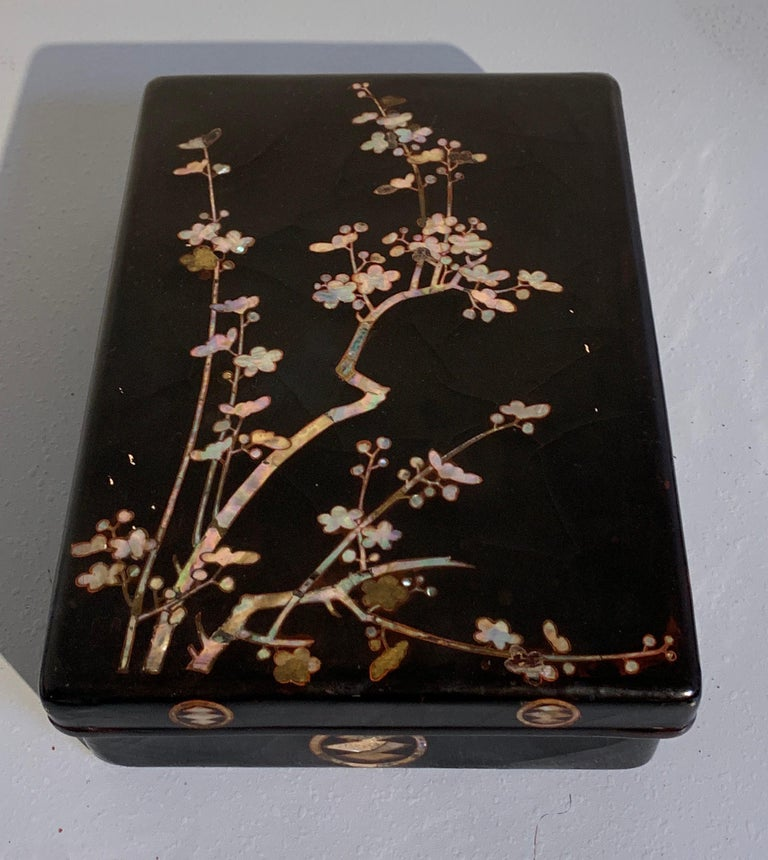 A fine and unusual Japanese black lacquer and mother of pearl inlaid box, Momoyama Period, 16th century, Japan.   The large box and cover featuring a design of blossoming plum branches rendered in mother of pearl on black lacquer. The interior a