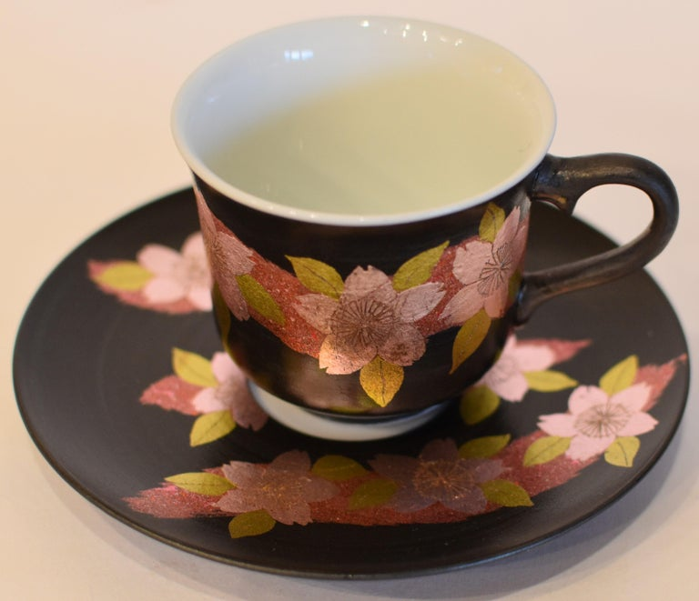 Extraordinary Japanese contemporary signed porcelain cup and saucer showcasing a stunning cherry blossom pattern in gold, pink and green on a black background. This is the work of a third generation master of a kiln located in the Imari-Arita region
