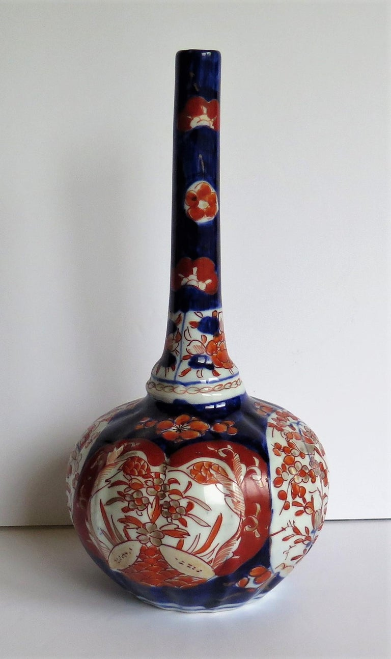 This is a very decorative Japanese bottle vase which we date to the early Meiji period of the 19th century, circa 1875.  This vase has a distinctive bottle shape with a tall stem neck having a shaped basal knop (swelling). The bulbous lower section