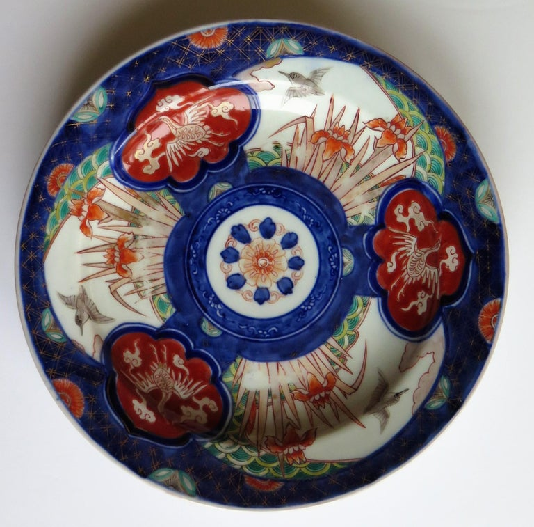 This is a very nice quality Japanese porcelain deep plate or bowl with an Imari pattern, dating to the mid-late 19th century, Meiji period, circa 1870.  The plate is hand decorated in varying shades of under-glaze cobalt blue, then hand enamelled