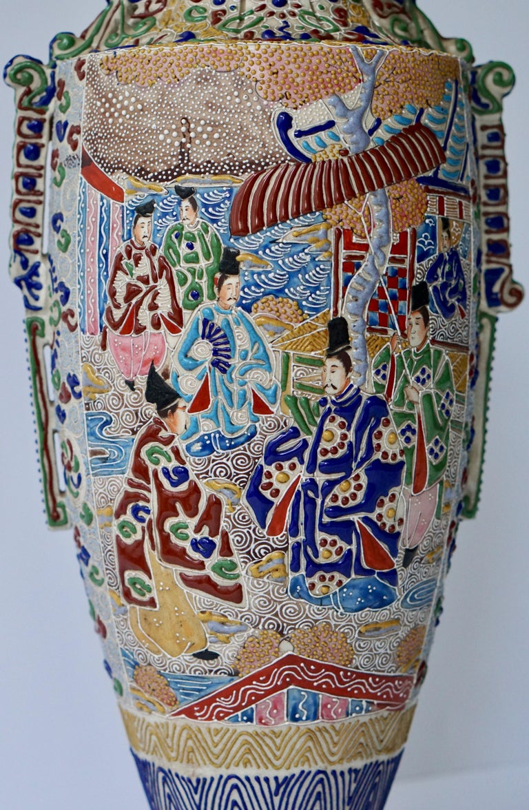 A mid-20th century Japanese Satsuma vase with figures.   Satsuma ware is a style of Japanese earthenware originally from the Satsuma region of what is today southern Kyushu. There are two distinct categories of this ware: The original plain dark