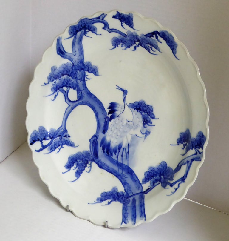 Beautiful Meiji Period blue and white Japanese Imari charger depicting a standing pair of cranes or storks on pine tree. The back has stylized depictions of waves. Appropriate firing marks centered on back and Japanese stamp Aoki Brothers of Arita.
