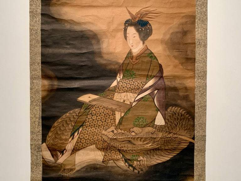 A powerful and brooding Japanese hanging scroll painting of the goddess Benzaiten riding a dragon, ink and color on paper, mounted on paper, with silk brocade, Taisho Period, early 20th century, Japan
