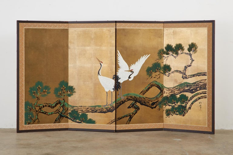 Colorful Japanese Showa period four-panel folding screen depicting a pair of Manchurian red-crowned cranes perched in a pine tree. Crafted on a dramatic gilt square background with ink and color pigments. Set in a lacquered wood frame with a silk