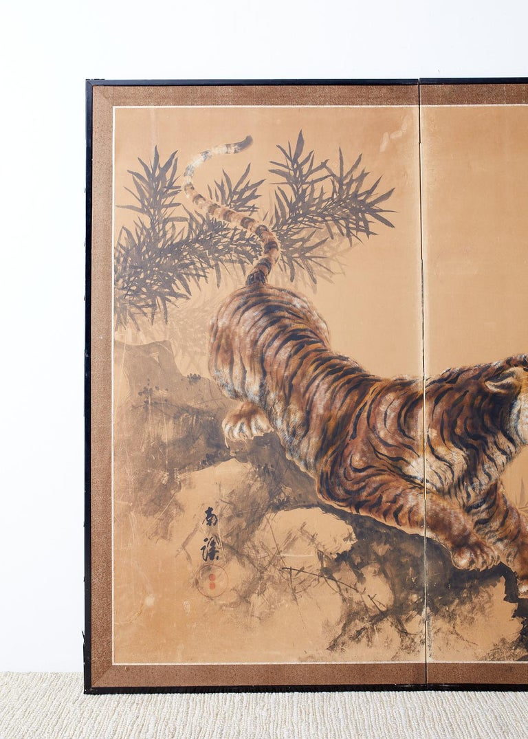 Captivating Japanese Showa period two-panel screen depicting a fierce tiger in bamboo. Painted in the Nihonga School style signed Nankei with an artist seal on the left side. Ink and color pigments on handcrafted paper. Set in a black lacquered