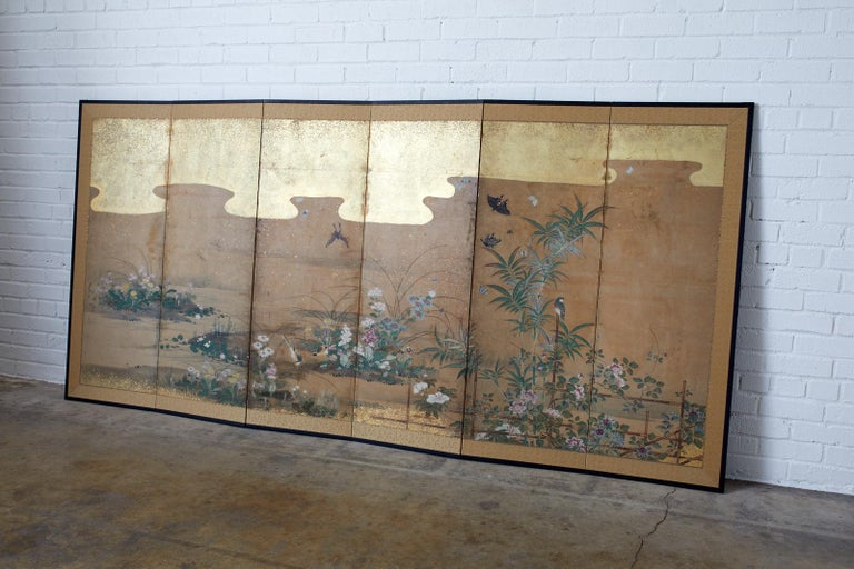 18th century Japanese six panel Edo period screen depicting flora and fauna landscape. Beautifully painted flowers with birds, insects, and butterflies at a water's edge. Ink and color pigments painted in the Kano school style with later added gold
