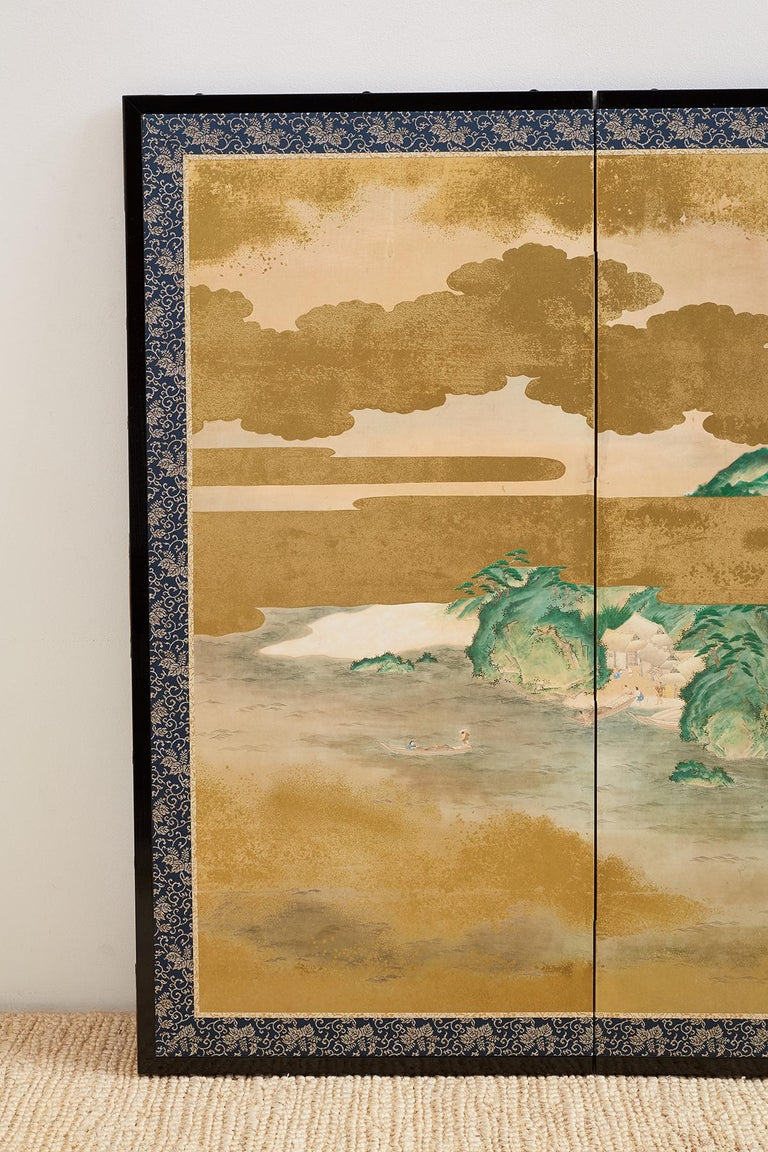 Large Japanese six-panel Byobu screen depicting an aerial view of a village with a river and mountain background. Painted in the Kano school style appearing to be from a narrative tale. Intricately painted villagers among houses and pagodas with