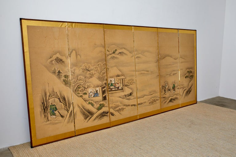 Large Japanese Meiji period six-panel screen depicting a winter landscape with a Chinese sage visiting friends in a country villa. Ink and vivid color pigments on mulberry paper mounted to a gilt background. Painted in the 19th century Kano school