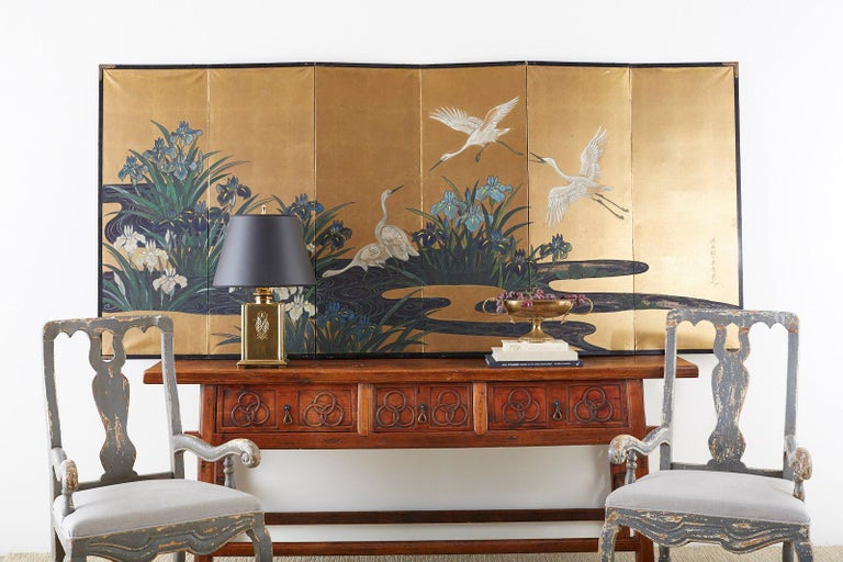 Captivating Japanese six-panel late Meiji/early Taisho Showa period screen featuring five egrets or herons in a water landscape. Painted with vibrant colored pigments over gold leaf squares with a rich, aged patina. The painting is signed on the