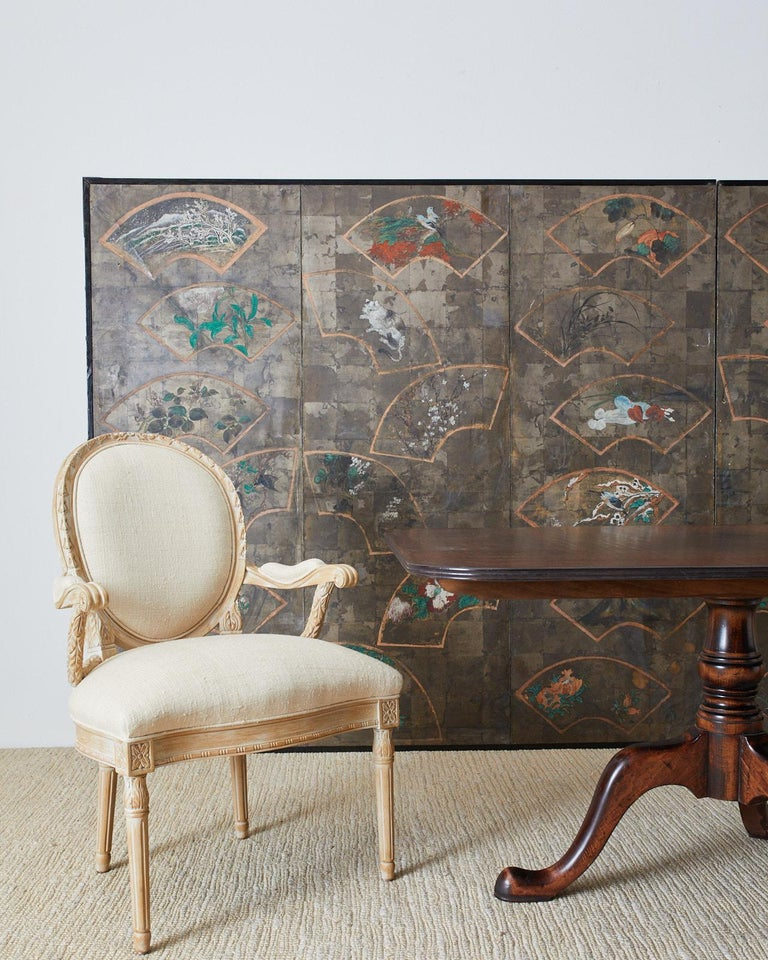 Large scale dramatic Japanese late 19th-early 20th century Meiji screen depicting numerous beautifully painted fans over a silver leaf square background. Originally a six-panel screen now conjoined into a large two-panel screen. The painted fans are