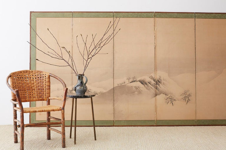 Monumental Japanese six-panel Meiji period screen depicting a serene snowscape mountain scene. Ink on paper made in the Maruyama school style late 19th-early 20th century. Bearing an inscribed date: Tenmei 1st year (1781) autumn. Signature reads